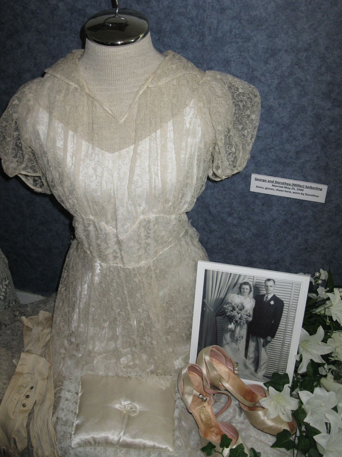 Vintage wedding dress on display with black and white photograph